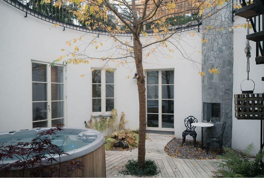 This Scandinavian-Style landscape has a tree in the middle of the area surrounded by cement walkways in the middle of four areas. Two of these areas are miniature gardens with ferns and shrubs. They pair with the outdoor dining area and the outdoor jacuzzi.