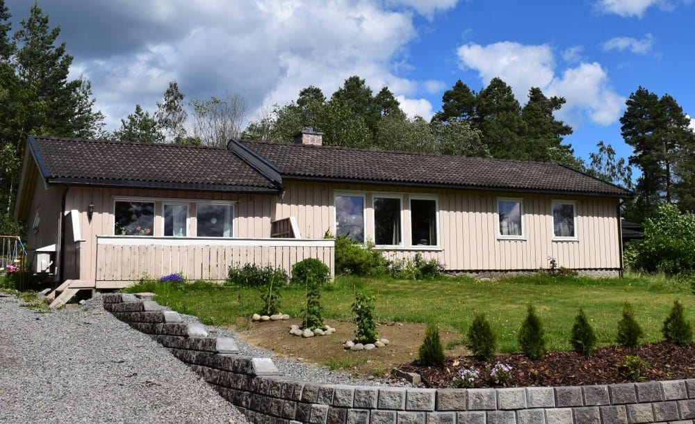 Scandinavian-style home with natural landscaping and stone brick hardscaping.