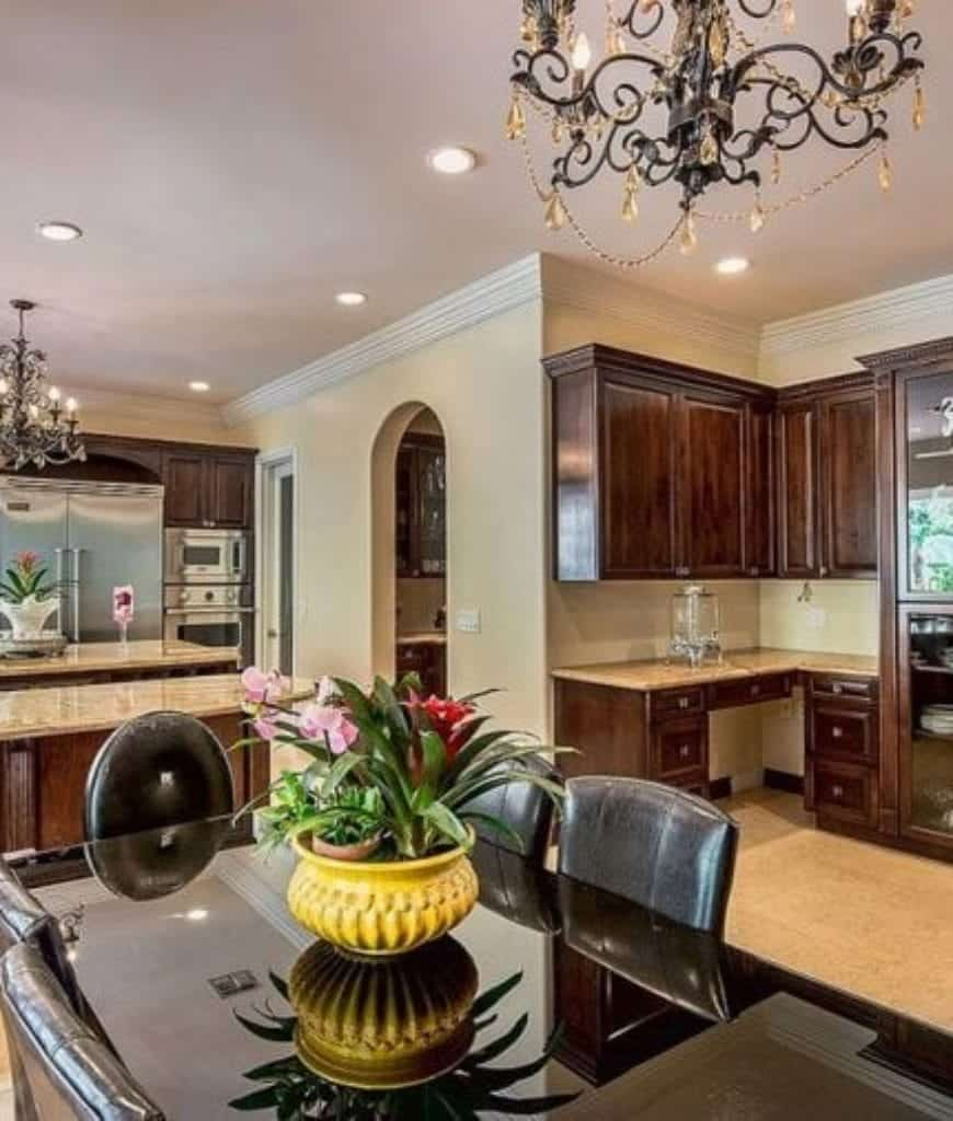 Gorgeous eat-in kitchen with double island bars and black dining set accented with a yellow flower vase. It is lighted by classic chandeliers and recessed ceiling lights.