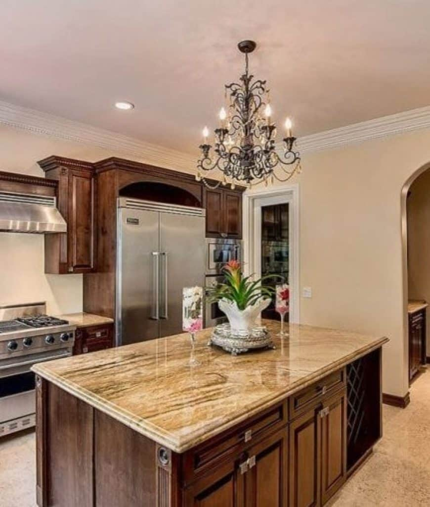 This kitchen offers stainless steel appliances and a wooden central island with built-in storage and crisscross wine rack lighted by a lovely candle chandelier.