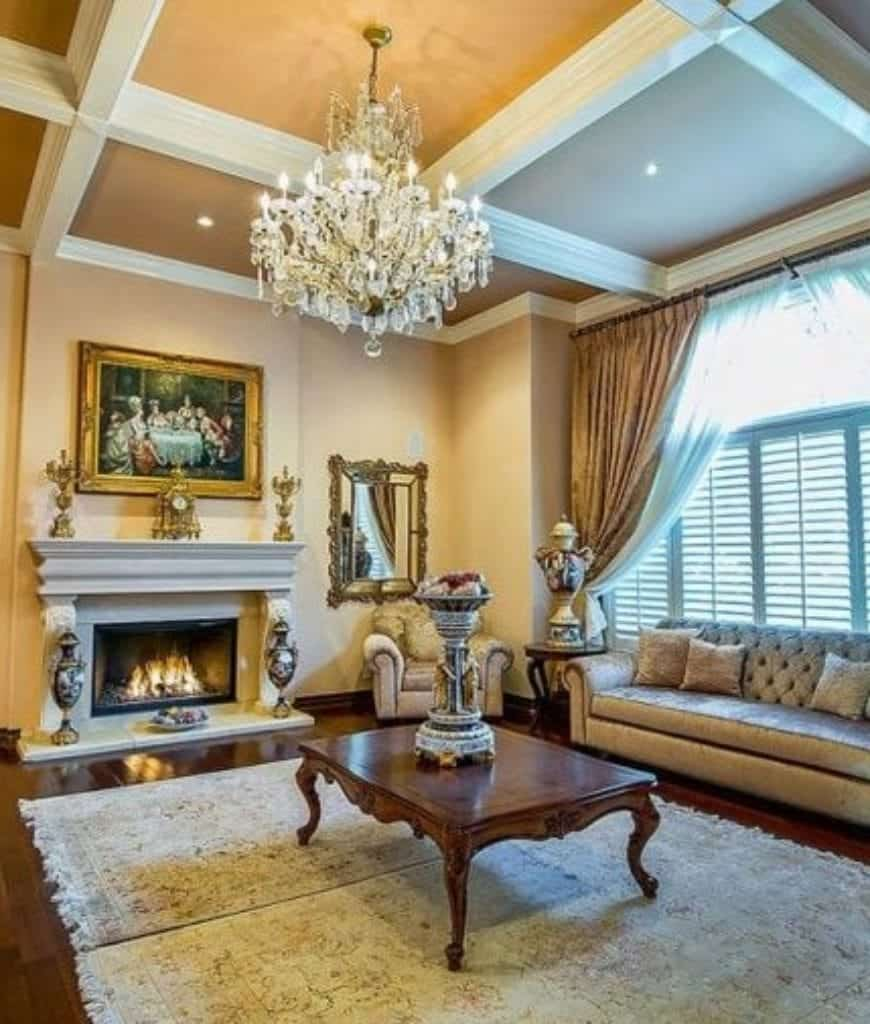 Elegant living room with classy tufted seats and a fireplace illuminated by a fancy chandelier that hung from the coffered ceiling.