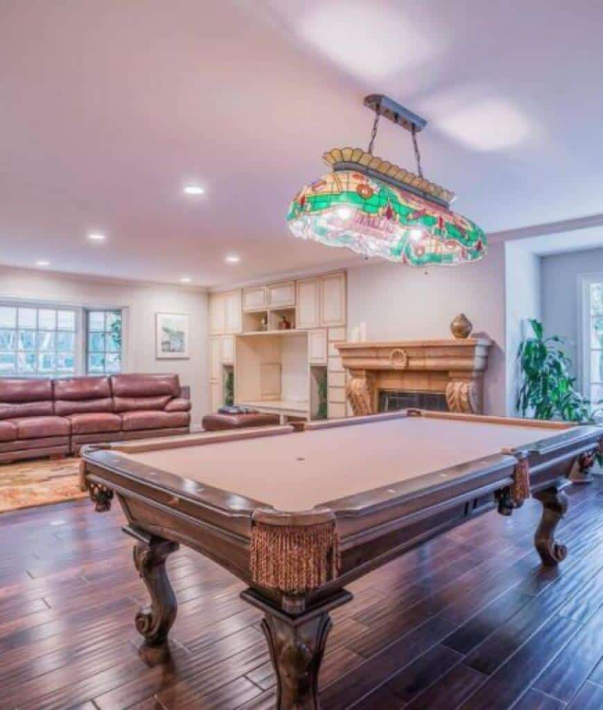 A gorgeous pendant light illuminates this family room showcasing a stone fireplace and wooden pool table that complements with the wood plank flooring.