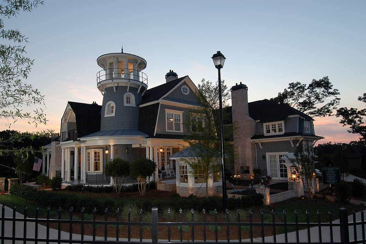 The centerpiece of this Craftsman-Style beach house is its viewing tower that looks like a lighthouse. It towers over the rest of the house and its dark roofs that complement the gray walls. This aesthetic is capped off with a landscape of well-maintained shrubs and trees.