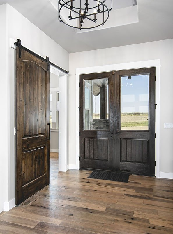 Foyer with a french entry door and a high tray ceiling mounted with a wrought iron chandelier. A barn door on the left slides open to a quiet den.