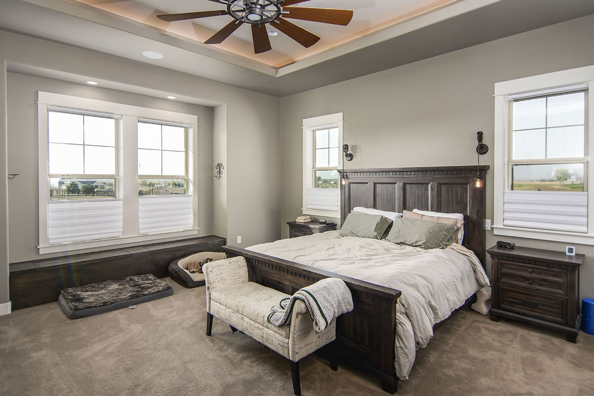 Primary bedroom with dark wood furnishings, gray walls, and a stunning tray ceiling accented with warm coved lighting.