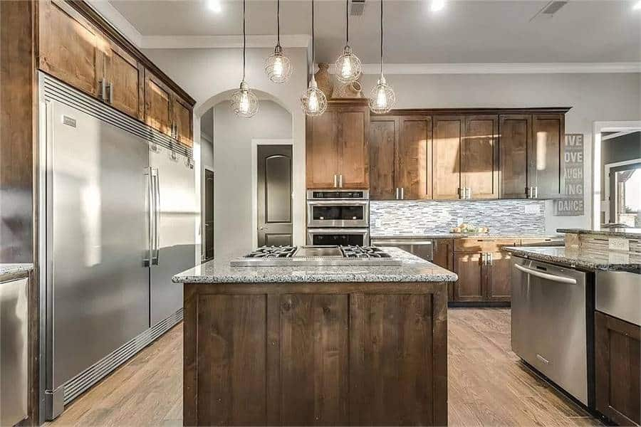 Large kitchen filled with wooden cabinetry, granite countertops, stainless steel appliances, glass globe pendants, and a striking backsplash.