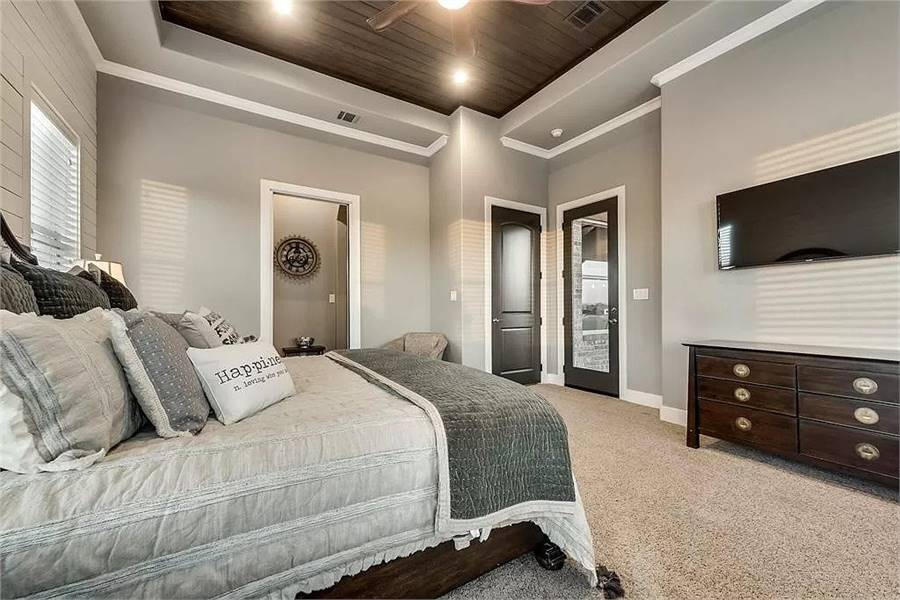 Primary bedroom with gray walls, carpet flooring, and a stunning tray ceiling clad in wood planks. The tone of the wood planks is echoed on the bed, dresser, and door for a seamless flow.