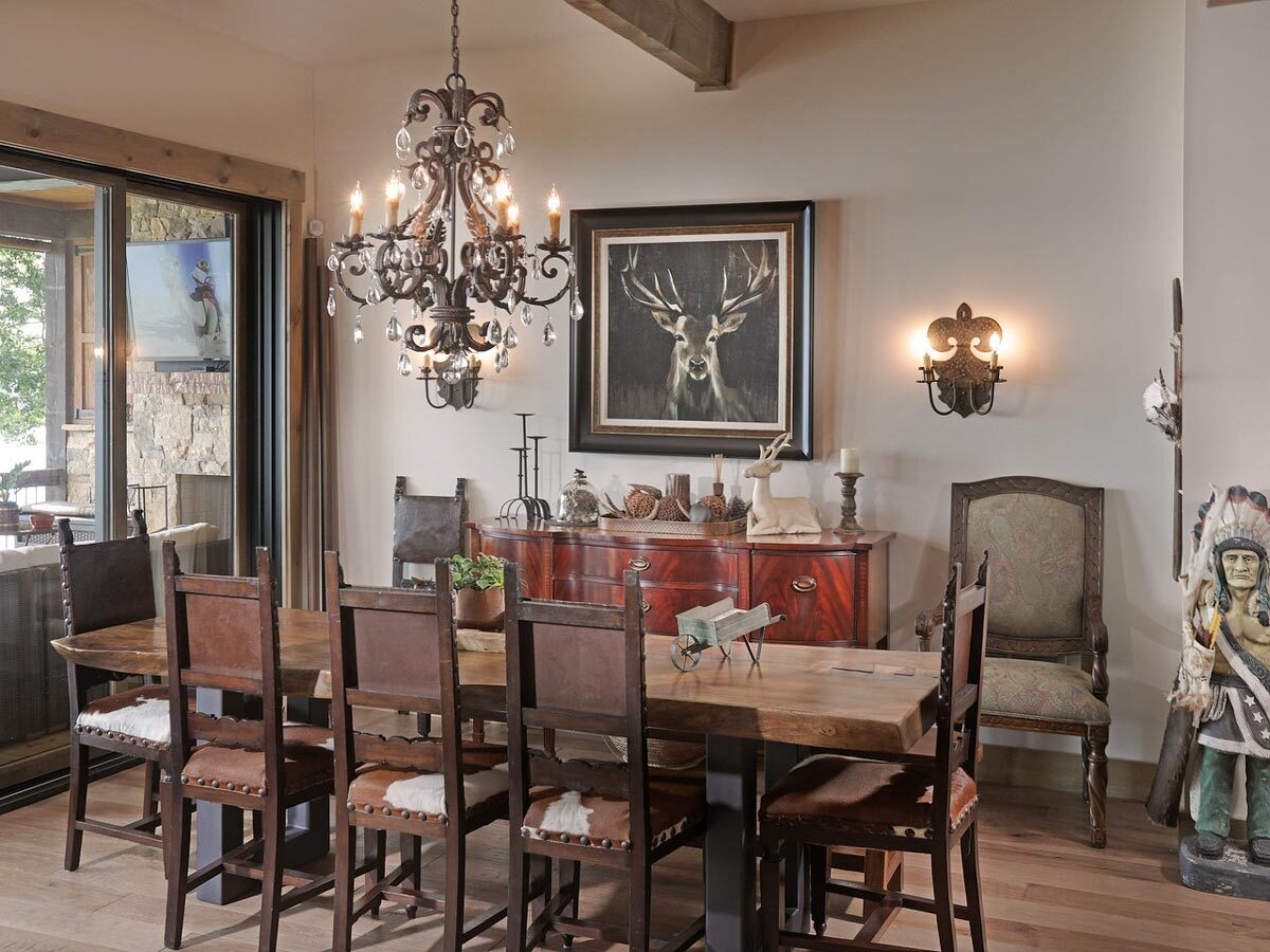 Craftsman dining room with wooden furnishings, an ornate wrought iron chandelier, and beige walls adorned by a deer artwork and warm sconces.