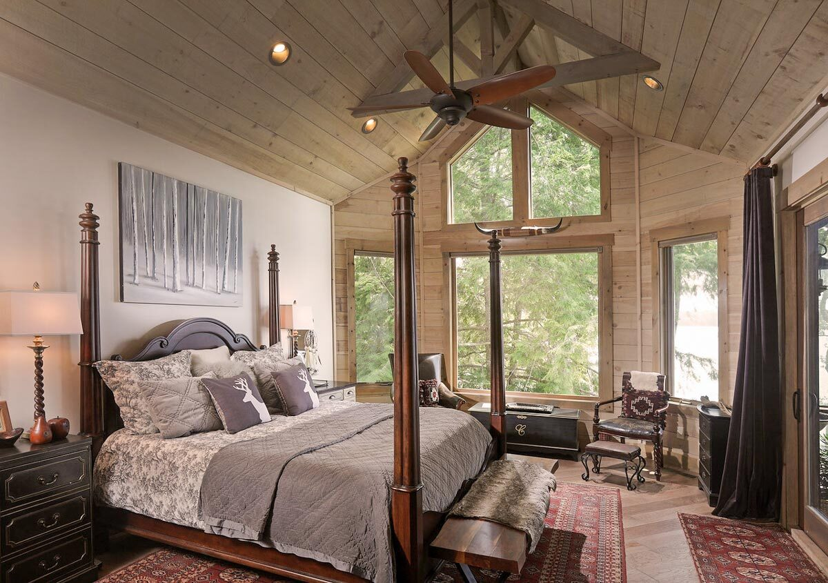 The primary bedroom features a four-poster bed, vaulted ceiling, and clerestory windows that bathe the room with natural light. Light wood planks enhance the cozy feel in the room.