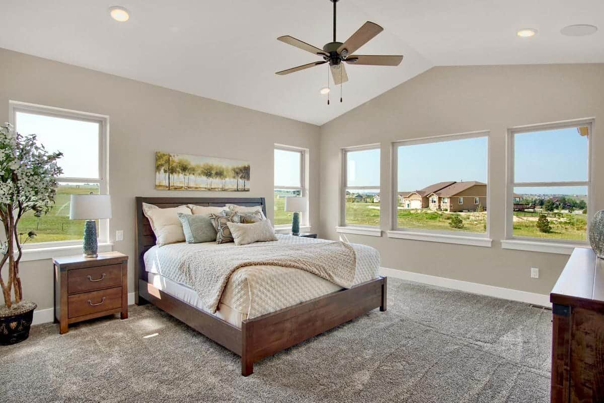 Surrounding windows flood this primary bedroom with natural light as it takes in incredible views of the expansive yard.