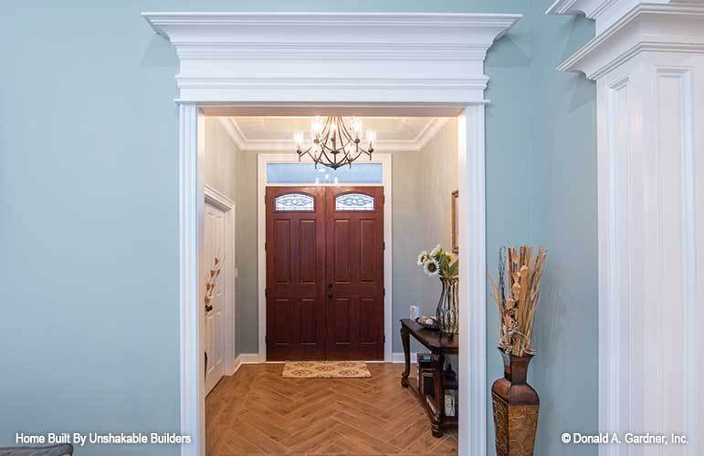Decorative white moldings frame this foyer with elegance. It has a double entry door and hardwood flooring arranged in a herringbone pattern.