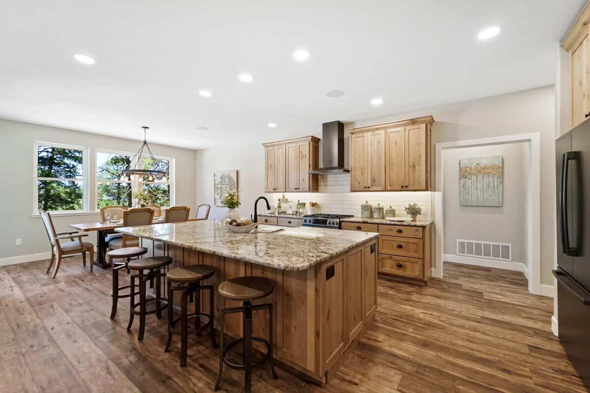 Spacious eat-in kitchen boasting a cohesive look achieved by the wooden dining set and natural wood cabinetry that match the wide plank flooring.