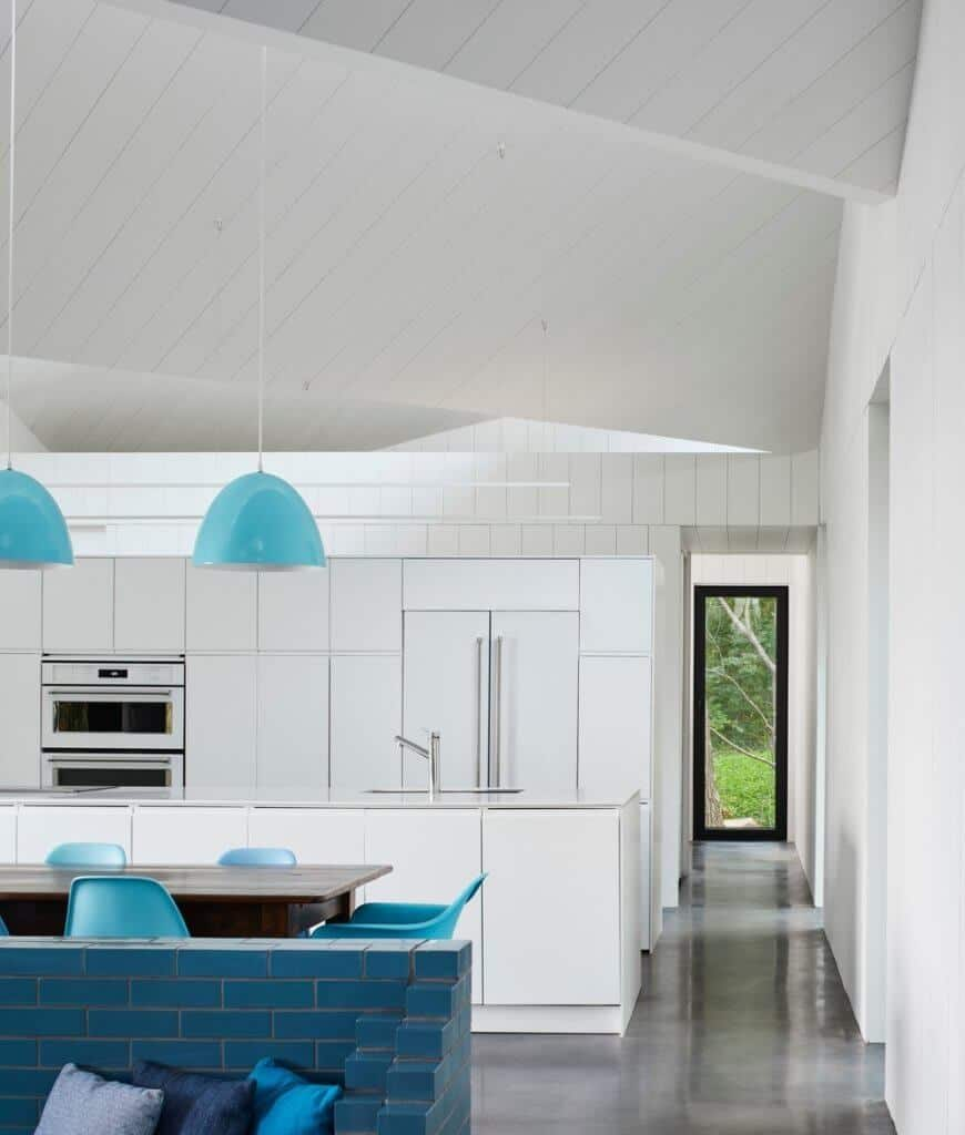 Contemporary white kitchen accented with blue pendant lights and modern chairs surrounding a dark wood dining table over concrete flooring.