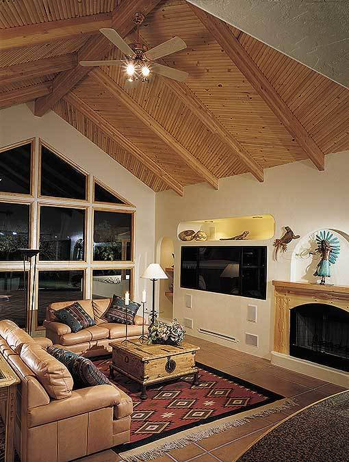 This is a simple Southwestern-style living room that is elevated by the patterns on the red area rug and the wooden cathedral ceiling that has exposed wooden beams. The brown leather sofas match the hue of this ceiling as well as the mantle of the fireplace.