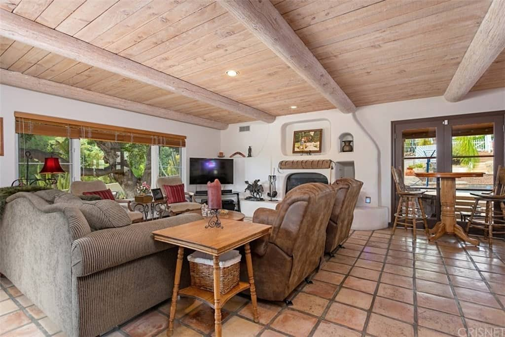 There is a wide wooden ceiling in this Southwestern-style living room that has exposed large wooden log beams. This goes well with the white wall that houses the fireplace and contrasts the terracotta flooring tiles. Those tiles complement the various cushioned armchairs and the large sofa.