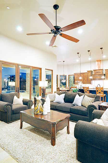 This bright Southwestern-style living room is contrasted by the black cushioned sofa and the pair of black cushioned armchairs paired with it to surround the wooden coffee table. This stands in the middle of the beige furry area rug below the large ceiling fan.