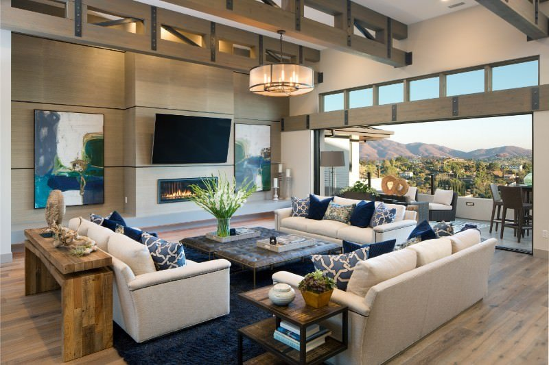 This is a marvelous Southwestern-style living room that boasts a modern fireplace in between abstract canvass wall arts. It has cream sectionals accented with blue patterned pillows that complement with the area rug that contrasts the sofas.