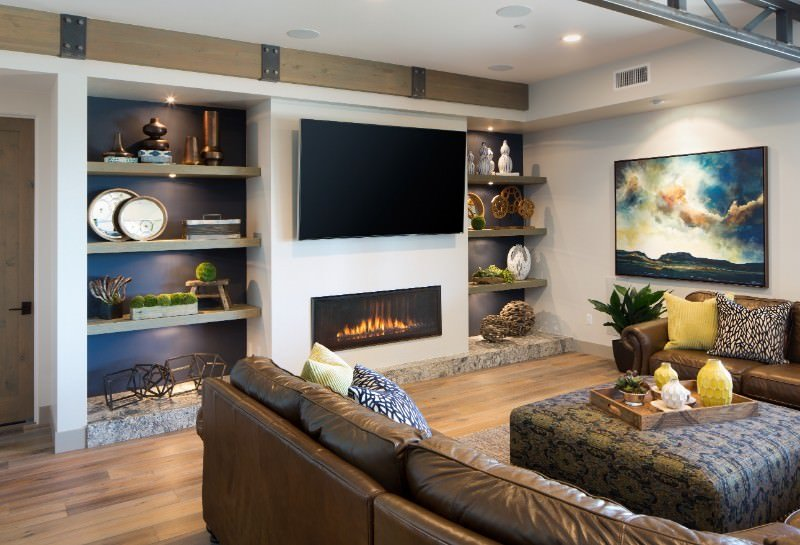 The modern fireplace of this Southwestern-style living room is right below the wall-mounted TV that is flanked by shelves embedded into the wall. These are filled with various decors that bring character to the room along with the colorful abstract painting behind the brown leather sofa.