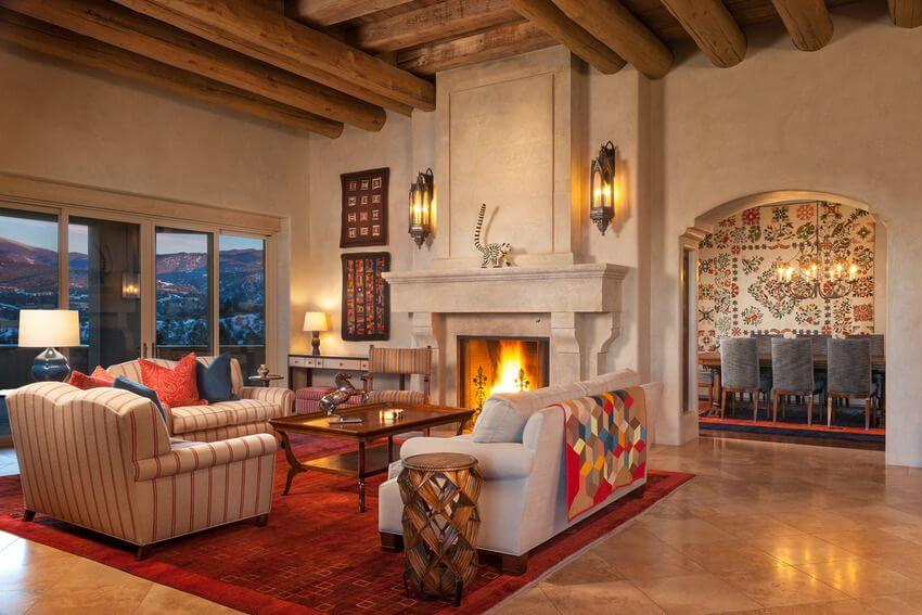 This Southwestern-style living room has an amazing high wooden ceiling with exposed wooden log beams. This partners well with the large fireplace and its large column that houses its mantle. Across from this is a bright red area rug that contrasts the light colors of the sofas.