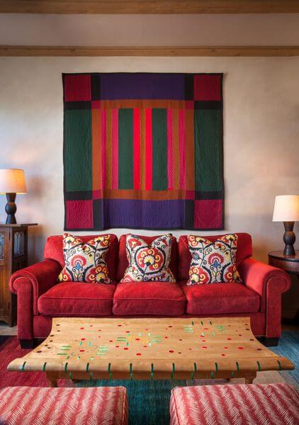 This Southwestern-style living room is dominated by the bold colors of the red velvet sofa and the colorful tapestry hanging on the white wall behind it. This is paired with a wooden coffee table with subtle colorful patterns on it matching the colorful area rug underneath.