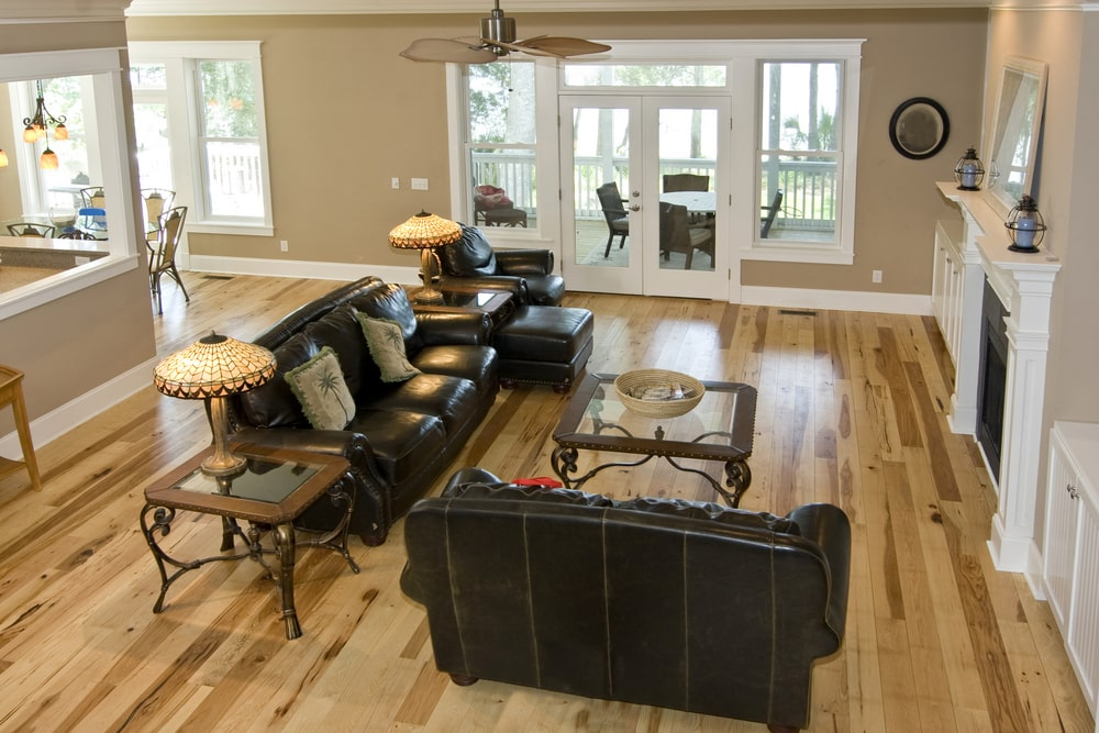 The beautiful maple hardwood flooring of this Southwestern-style living room is contrasted by the black leather sofa set paired with a glass top end table that matches with the glass top coffee table by the fireplace that has a white mantle.