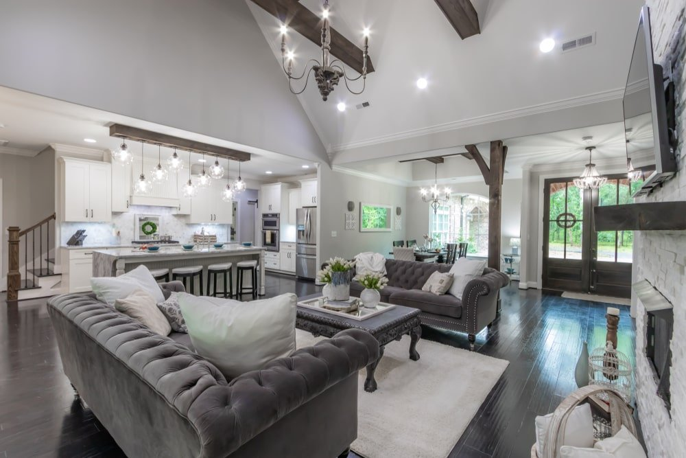 This elegant Southwestern-style living room has black hardwood flooring that matches with the black velvet cushioned tufted sofas and their black coffee table on the light gray area rug by the fireplace. This is topped with a white cathedral ceiling that has exposed wooden beams.