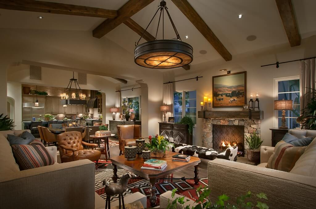 This charming and comfortable living room has a distinct Southwestern-style vibe to its patterned area rug that gives a nice contrast to the brown leather tufted armchairs and the beige sofa set around the brown wooden coffee table underneath the large round pendant light.