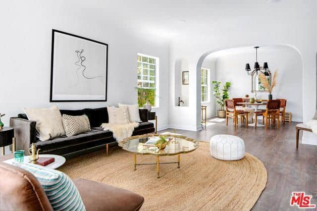 This is a brilliantly white interior with an arched entryway over wooden floors topped with a woven wicker area rug. Dark elements that are paired with earthy tones are strategically placed to balanced the stark whiteness. There is a touch of modernism in some of these elements that seem to fit in with the overall aesthetic.