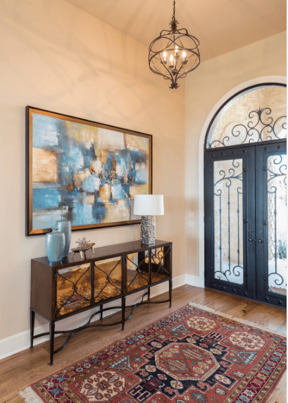 The intricate iron details of the glass double doors match the iron chandelier hanging over the colorful patterned rug on the wooden floor. The lovely wall mounted abstract painting above the console table is an amazing divergence from the plain beige walls of this Spanish foyer.