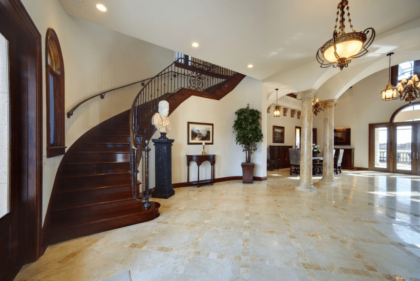 Elegant marble floors and columns give a stark contrast to the dark wooden main doors and staircase. The balancing elements are brought by the white walls, potted plant, and the eclectic statue bust by the door. All of these are illuminated by the semi-flush lights mounted on the white ceiling.