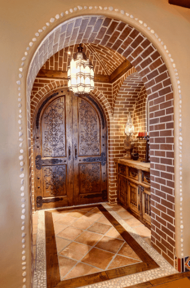 The brick patterns of the walls and groin vaulted ceiling in this Spanish foyer gives it a unique personality. The warm yellow light from the curious pendant lighting in the middle of the room gives a warmness to the traditional wooden double doors that harmonize with the cabinet drawers on the side.