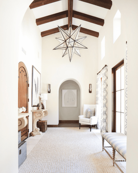 The centerpiece of this Spanish foyer is the polyhedron pendant lighting hanging from the cathedral ceiling with exposed wooden beams. This is a predominantly white foyer with white walls, white area rug, white arched entryway, and white furniture that is brightened further by the glass French door.