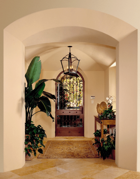 The groin vaulted ceiling of the foyer is placed in between the arched entryway and the arched gate-like patterned door. This main door showcases the beauty of the landscaping outside that is mirrored to the interior by the potted plants.