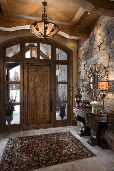 A Spanish foyer with varying patterns and textures that are fused with warm hospitality for the people entering it. The wooden main door with side lights and top lights are mirrored into the exposed beams of the ceiling and console table. The peculiar wall-mounted mirror contrasts the stone wall while the colorful patterned rug contrasts the white grayish marble floor.