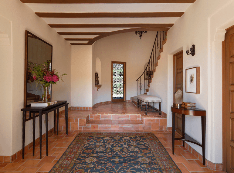 Tradition meets modern elements in this Spanish foyer. The beam designs of the regular white ceiling adapt the modernism that is showcased by the wall-mounted mirror behind the console table. A sense of tradition is invoked by the pairing of the terracotta floor with a colorful patterned rug, wooden doors, and dark wood console tables.
