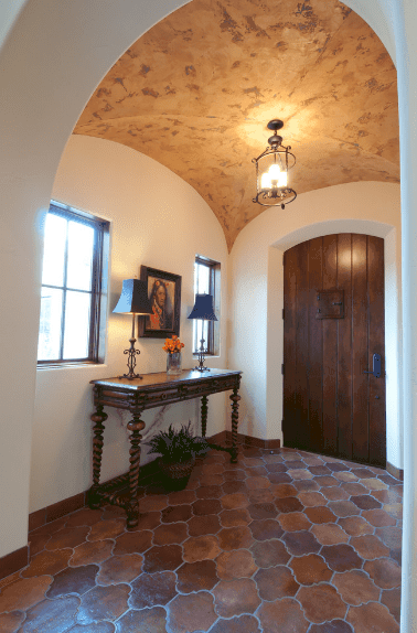 The terracotta patterned floor is partnered with a groin vault ceiling with a semi-flush mount light. The marble patterns of the ceiling and its beige color makes it stand out in this traditional Spanish foyer. The dark wooden console table along with the arched wooden door is emphasized by the wall-mounted painting in between the two windows.