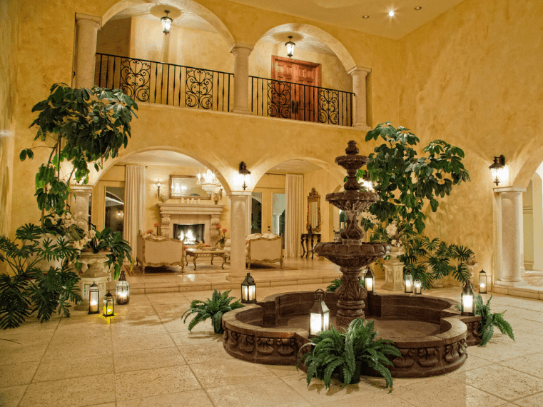 This traditional Spanish foyer is spacious and looks almost like a courtyard with its own landscaping. The main feature is the huge stone fountain in the middle that is adorned with lanterns and potted plants. The warm yellow lights coming from the lanterns and wall-mounted lamps are supplemented by the pin lights from the high ceiling. The scenery is capped off by rough stone floors that go well with the greenery.