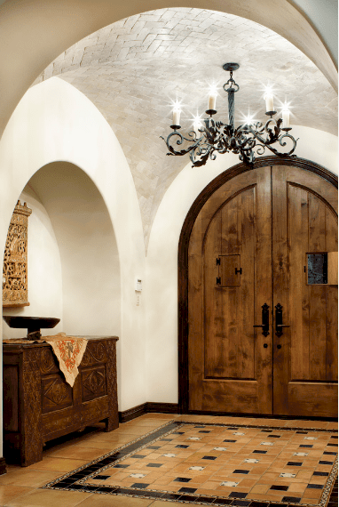 A simple and bright foyer with a groin vault ceiling and a dark iron chandelier that brightens the white walls and brown-tiled floor. The brown tiles of the floor blend well with the wooden double doors and carved cabinet fitted into the alcoved wall on one side.