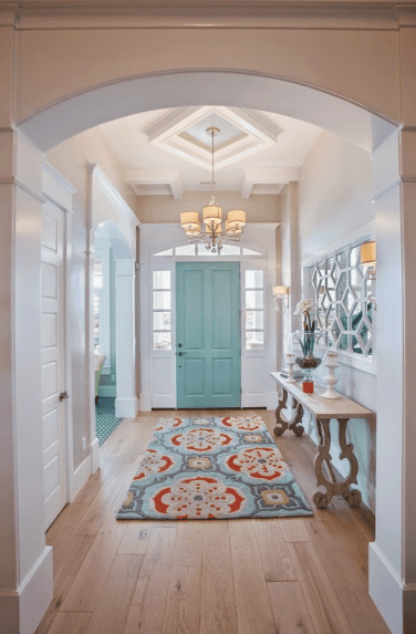 The matching bright hues of the main door and patterned rug offer a friendly and delightful welcome to this foyer with a coffered ceiling. Hanging from this ceiling is a modern chandelier that fits into the chic theme and is reflected in the built-in mirror above the console table.