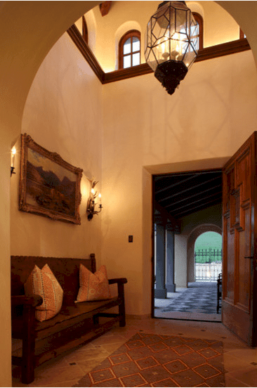 A warm and welcoming Spanish foyer that offers a comfortable long bench against the wall by the wooden door. The high ceiling and majestic pendant glass lantern reciprocate the geometric patterns of the marble floor and the patterned rug. A touch of sophistication comes from the wall-mounted painting above the wooden bench.