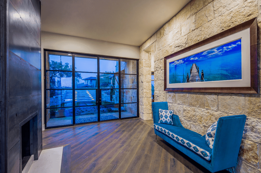 A Spanish foyer that invokes the sense of being beneath the waves of the sea with its bluish French glass doors, blue bench and even the wall-mounted framed photo above it. This is further augmented by the rough stone wall that is the color of sand. Across from the wooden floor from the bench is a fireplace that seeks to balance the coldness of the bluish hues.
