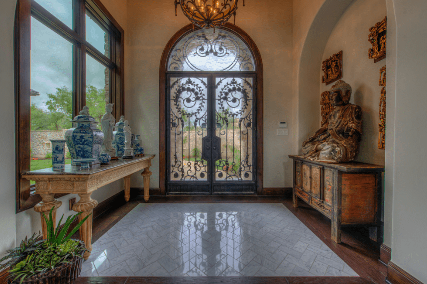 The natural light coming from the windows and glass doors is reflected beautifully on the white floor tiles and white walls. This light is supplemented by the dome-shaped chandelier with patterns similar to the patterns of the doors. An additional Eastern flavor is added to the mix with the decors on both sides of the Spanish foyer.