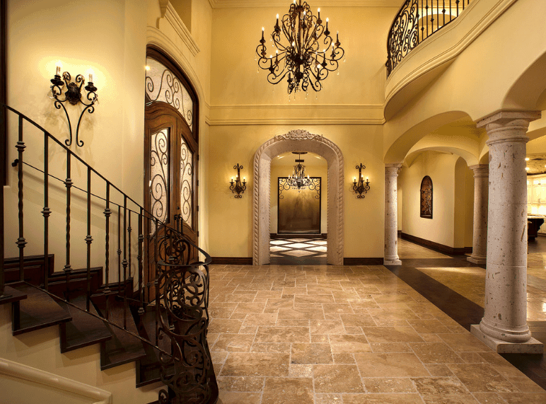 The dark ironworks and patterns in this foyer stand out against the stoneworks and solid beige walls. These elaborate iron designs are customized into the railings of the stairs, loft, doors and even the massive chandelier hanging from the high ceiling. The wall-mounted lamps are derived from this chandelier and serve as a good contrast to the straight lines of the marble floor and wall finishing.