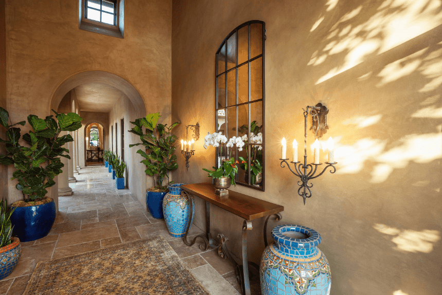 Rustic and traditional, this Spanish foyer seems warm and welcoming due to its earthy tones, worn patterned rug and warm light coming from the wall mounted lamps. The bluish urns and potted plants give a splash of color and a semblance of water on dry soil. The traditional console table is an elegant touch, as well as the mirror above it.
