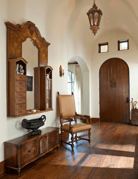 The white walls and coved ceiling that pairs with the arched entryway and wooden main door. The wooden elements are the stand-out quality of this quaint Spanish foyer. The almost antique facade of the wooden floor and cabinets surrounding the mirror is coupled with the pendant lantern light hanging from the ceiling.