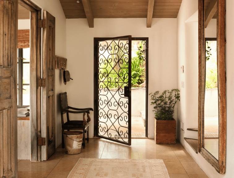 The striking gate-like metallic main door has intricate spiral patterns that give a view of the landscaping. This entryway gives an outdoor quality to the Spanish foyer which is augmented by a wood-potted plant, wooden doors and a large wall-mounted mirror with a wooden frame. They are paired well with a traditional armchair and a hat rack mounted above it.