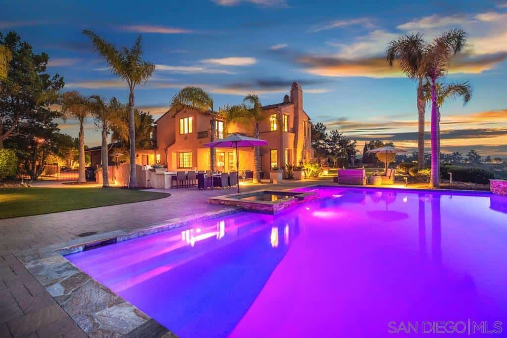 The stand-out feature of this poolside Spanish landscape is the brilliant purplish lights illuminating the whole pool giving it an otherworldly quality. It almost overshadows the beautiful stonework that makes up the walkway surrounding the pool. The sporadic placement of tall tropical trees completes the aesthetic.