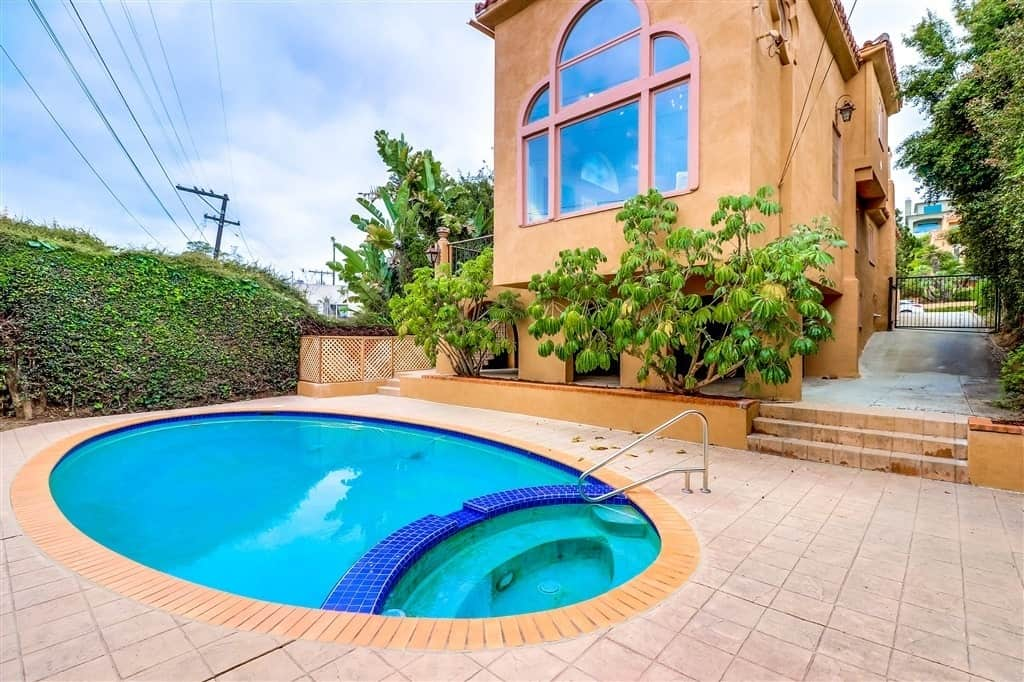 This backyard showcases an oval pool surrounded by the terracotta floor that is bleached to match the exterior color of the beige house. A ledge beside the pool is filled with soil and planted with a couple of trees that stand in contrast to the blue waters of the pool and the massive tinted window of the house.