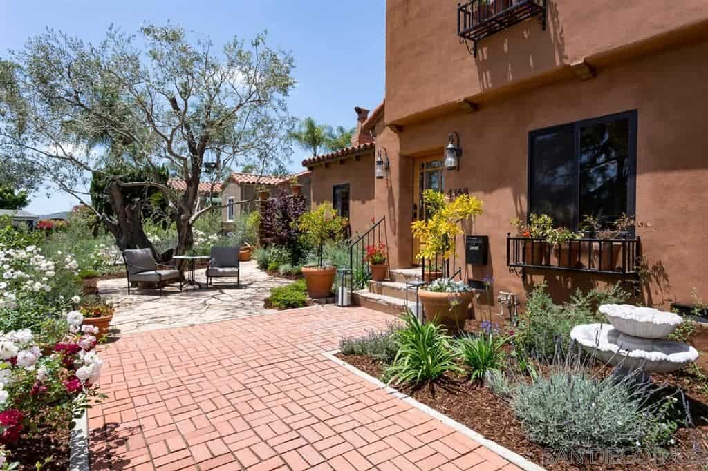 The terracotta walkway of this Spanish landscape serves as a nice background for the abundant variety of colorful potted plants surrounding it. A small white stone fountain sits by the window that has a metallic wall-mounted ledge with potted plants. The main feature is a huge gnarled Eucalyptus standing over a couple of lawn chairs and a small table.