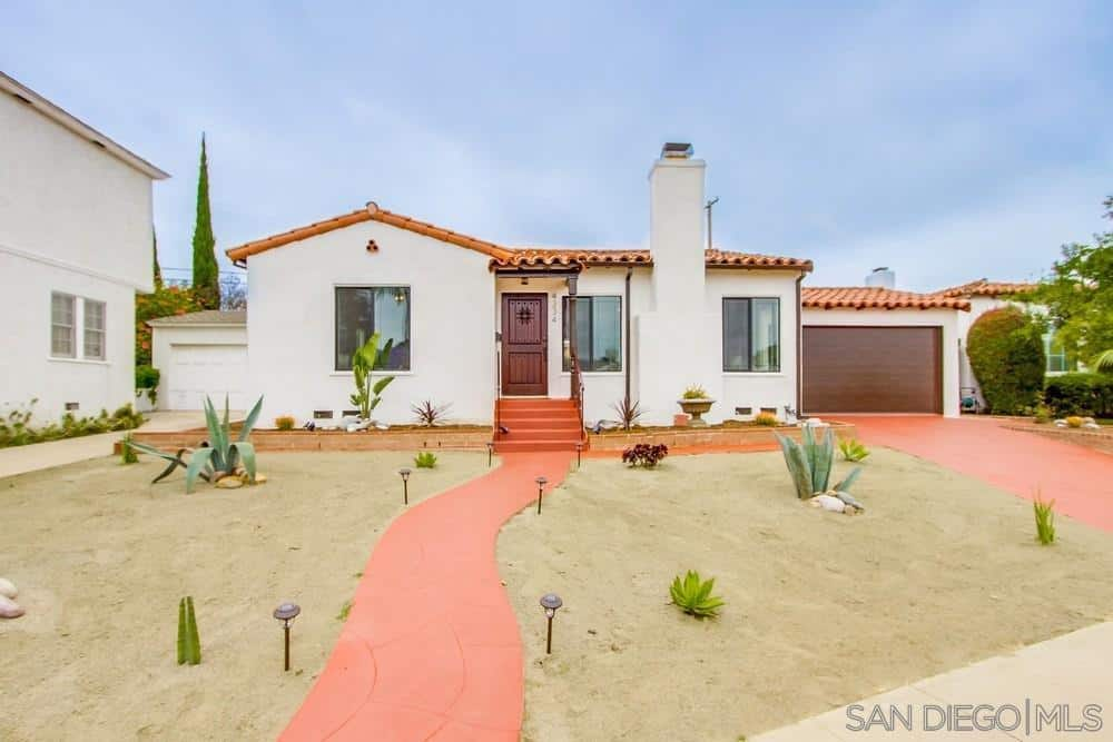 This a picturesque scenery that features a desert landscape that is peppered with succulents and aloe vera on a sand-like soil. The walkway and driveway are built with terracotta materials that bear subtle patterns and lined with lights sticking out of the ground.